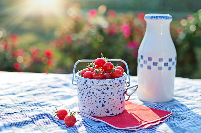 Red cherries in white and blue ceramic bucket