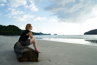 Woman wearing black shirt with gray short sitting on brown slab near the body of water during daytime