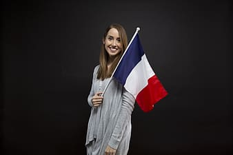 Woman wearing gray cardigan holding red, blue, and white flag