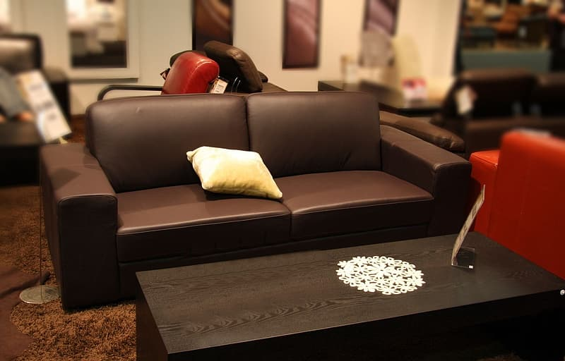 Brown leather sofa with pillow near coffee table