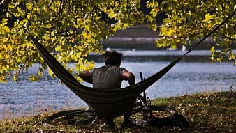 Woman in black shirt sitting on hammock near body of water during daytime