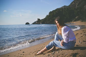 Woman sitting near seashore
