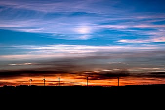 Silhouette of five turbines during golden hour