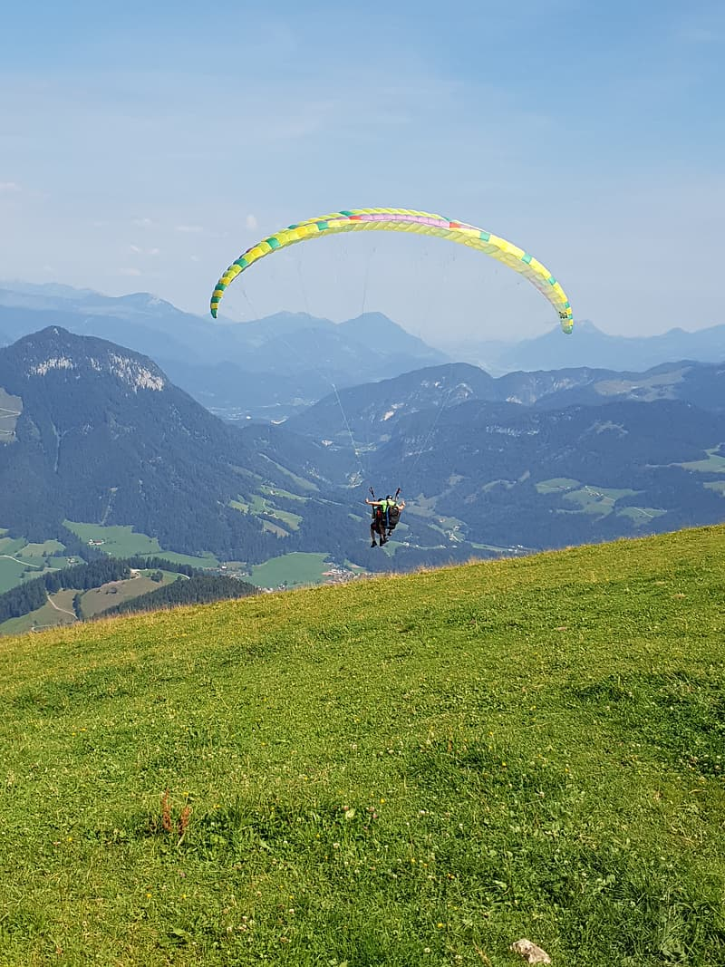 Person riding parachute over green mountains during daytime
