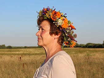 Woman wearing white scoop neck shirt with floral headdress