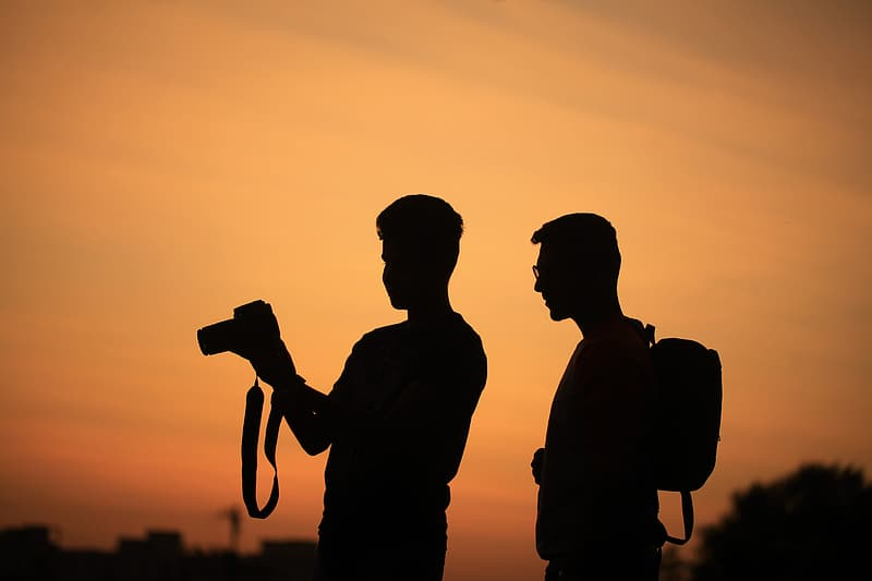 Silhouette of two men carrying camera and backpack during sunset