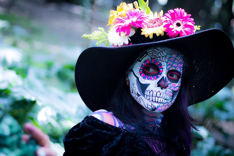Woman in black dress wearing black hat with sugar skull face paint