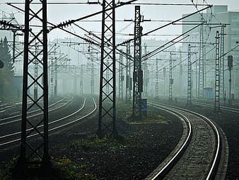 Photo of black train rail surrounded by transmission towers
