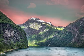 Green and white mountain beside body of water during daytime