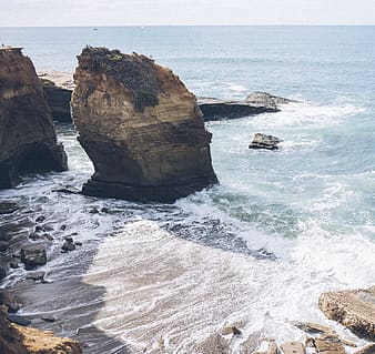 Brown rock formation near cliff side overlooking sea