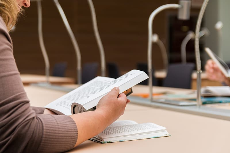 Close-up photo of woman with gray long-sleeved shirt reading book