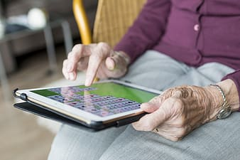 Person with purple button-up jacket using white iPad close-up photo