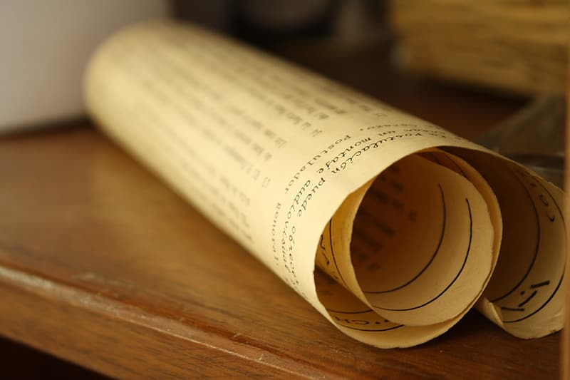White scroll of paper on brown wooden surface