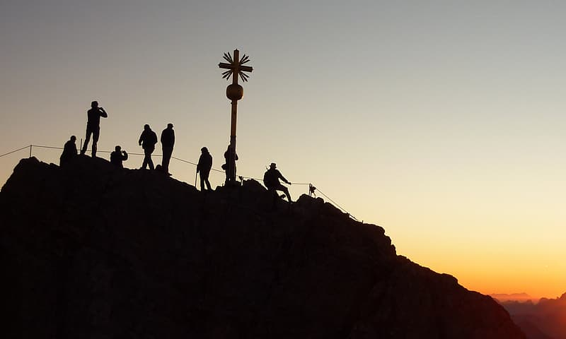 Silhouette of group of people on hill during golden hour