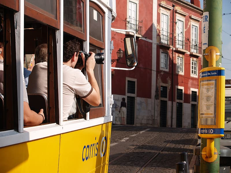 Woman in white tank top and black shorts sitting on yellow and white bus during daytime