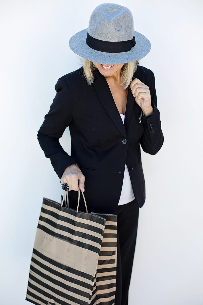 Person in black blazer holding brown and white woven hat