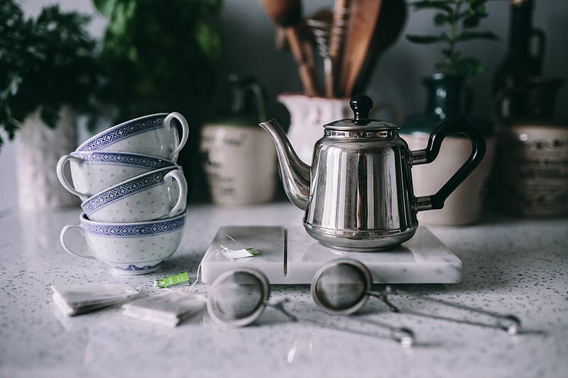 Stainless steel teapot on table