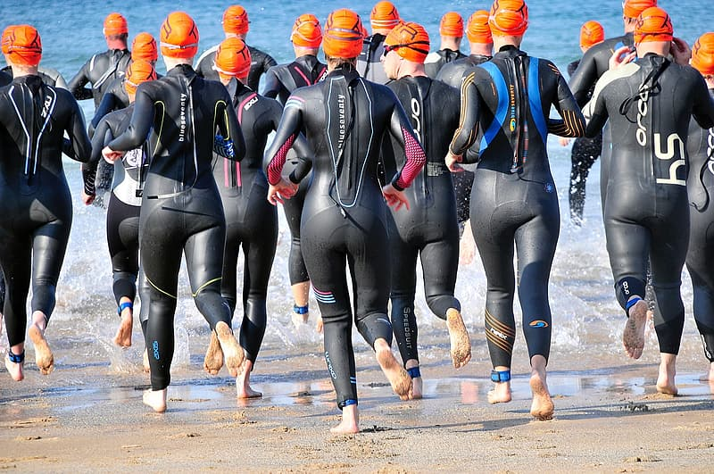 People wears black wetsuits while running together on the beach at daytime