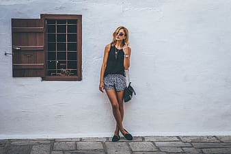 Woman in black sleeveless top standing in front of white wall