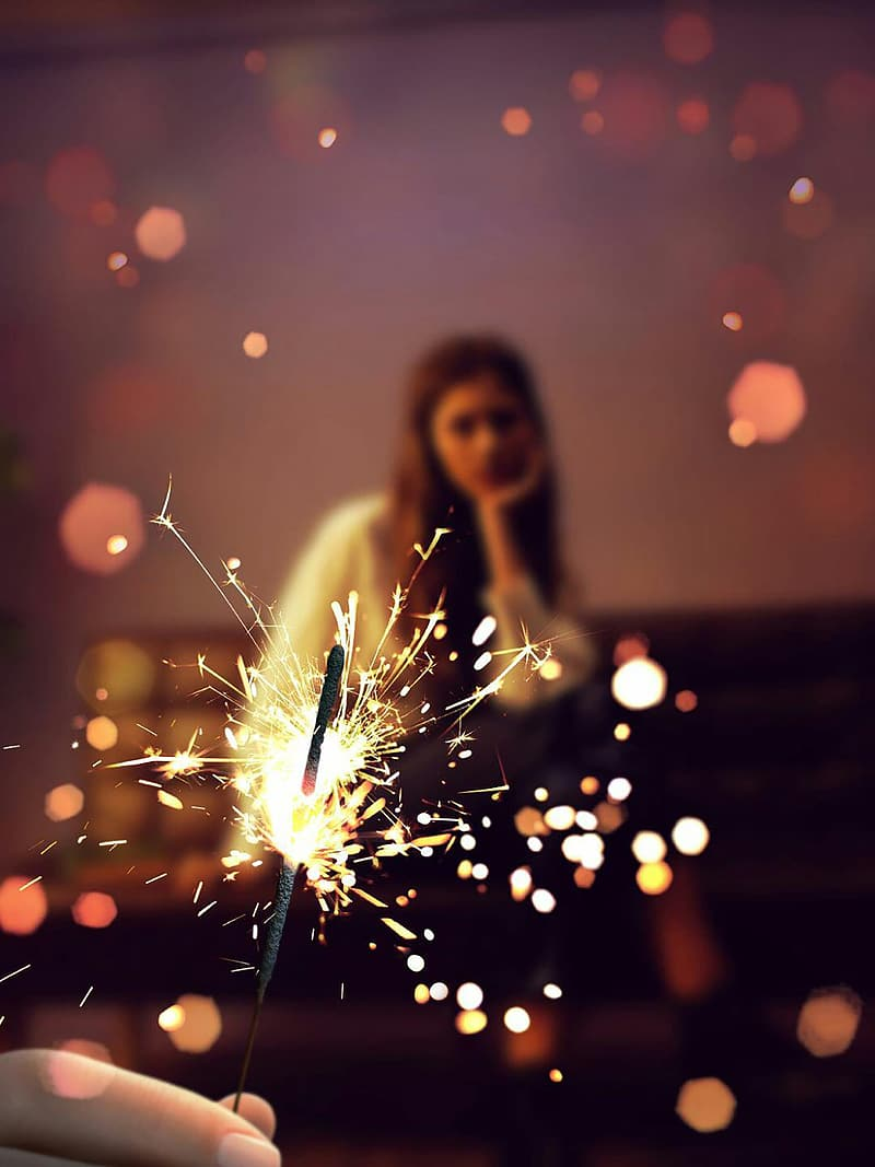 Close-up photo of person holding firecracker overlooking woman sitting on chair