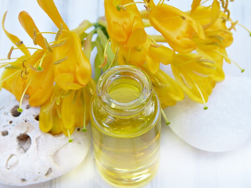 Yellow flowers in clear glass jar