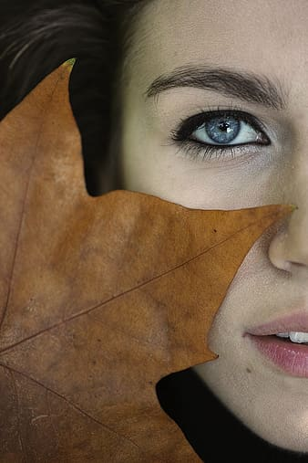 Closed-up photo of brown maple leaf on woman's face