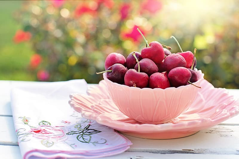 Pink bowl of red cherry fruits beside pink floral cloth