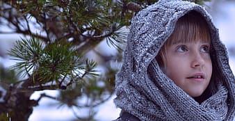 Girl with blond bangs wearing gray scarf outside during winter