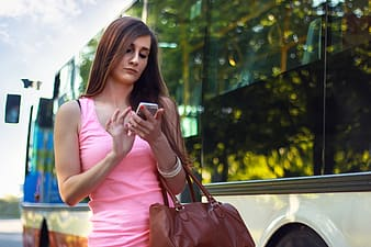 Woman in pink tank top holding smartphone
