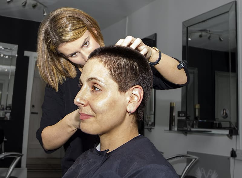 Woman having a short hair cut style by a woman beautician
