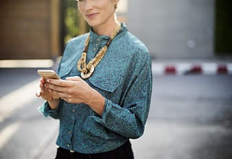 Woman in blue sweater holding white smartphone