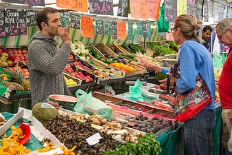 Woman standing in front of vegetable store