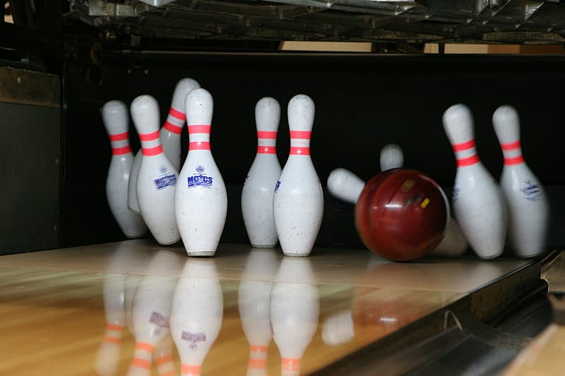Red bowling ball beside pins
