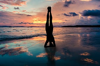 Silhouette of woman standing on water during sunset