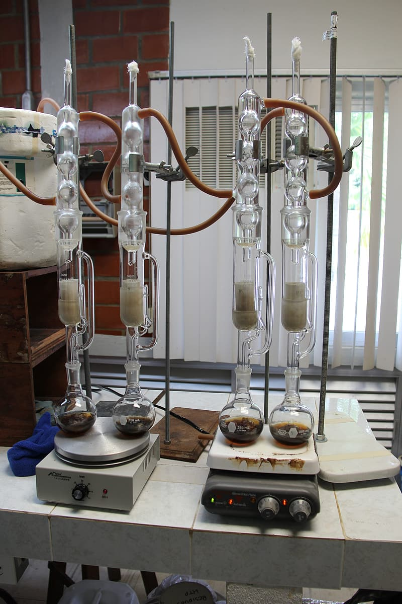 Four clear glass laboratory equipments