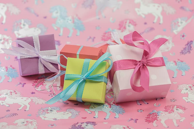 Several assorted-color boxes on top of pink textile
