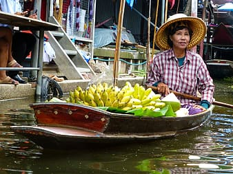 Woman riding boat with bananas