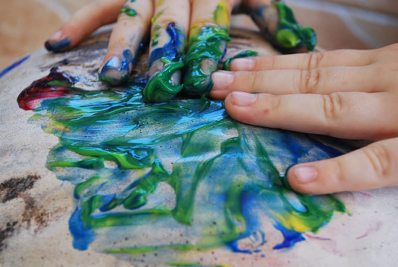 Person with green paint on hand