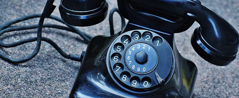 Vintage black rotary phone on gray surface
