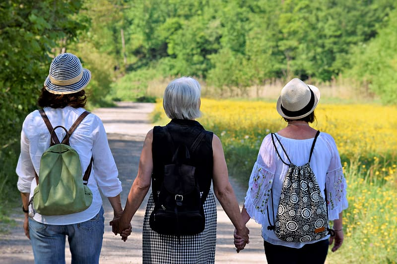 Three women holding their hands while walking on road
