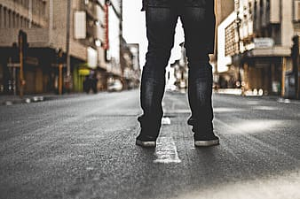 Person in black jeans standing on road
