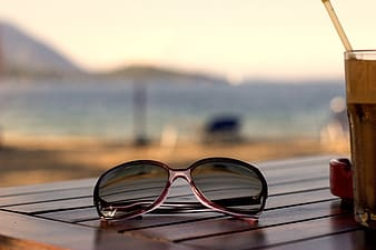 Selective focus photography of aviator-style sunglasses on wooden table