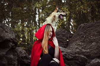Woman in Red Riding Hood costume sitting on black rock
