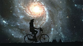 Silhouette of person riding bicycle under white clouds during daytime