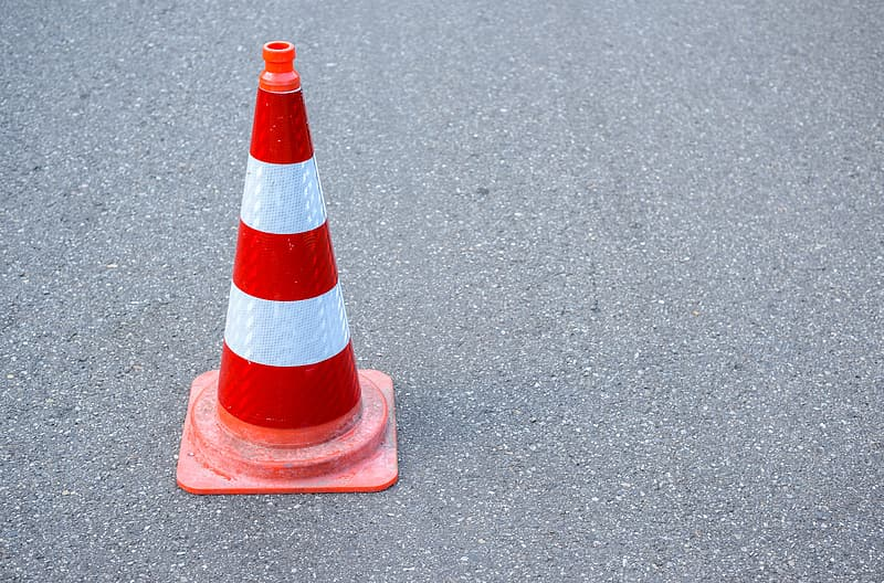 Red and white traffic cone on gray concrete floor