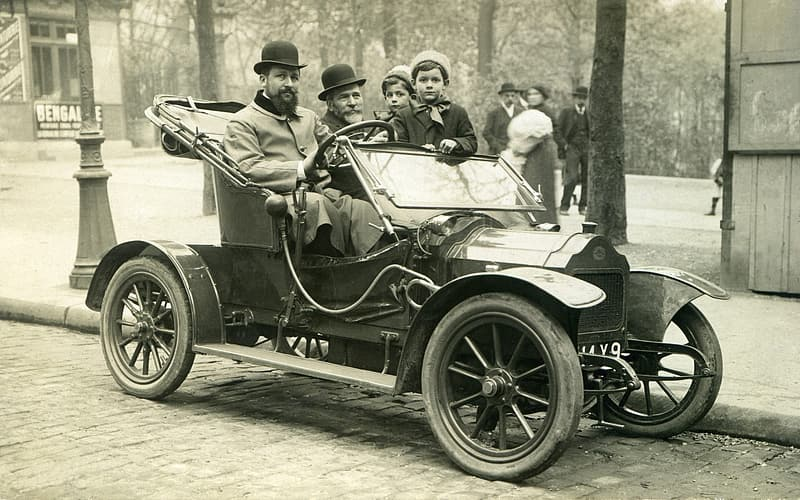 Grayscale photography of group of people on antique car