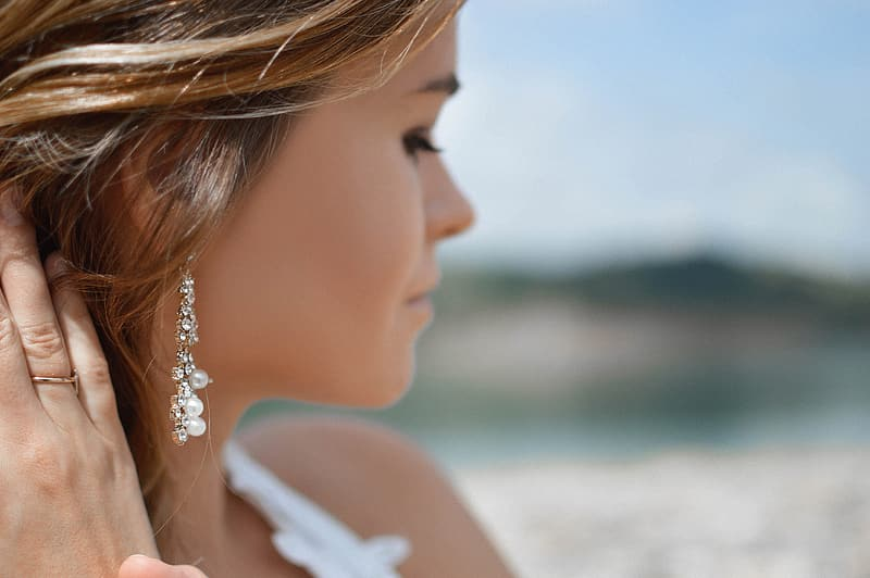 Shallow focus photography of woman wearing white top and dangle earring