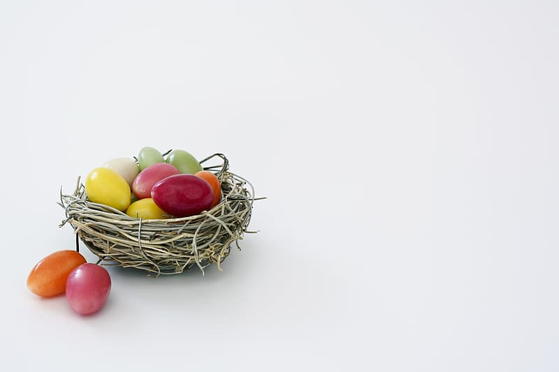 White wicker birds nest and assorted-color eggs