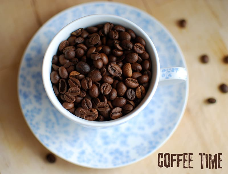Brown coffee beans on white and blue ceramic bowl