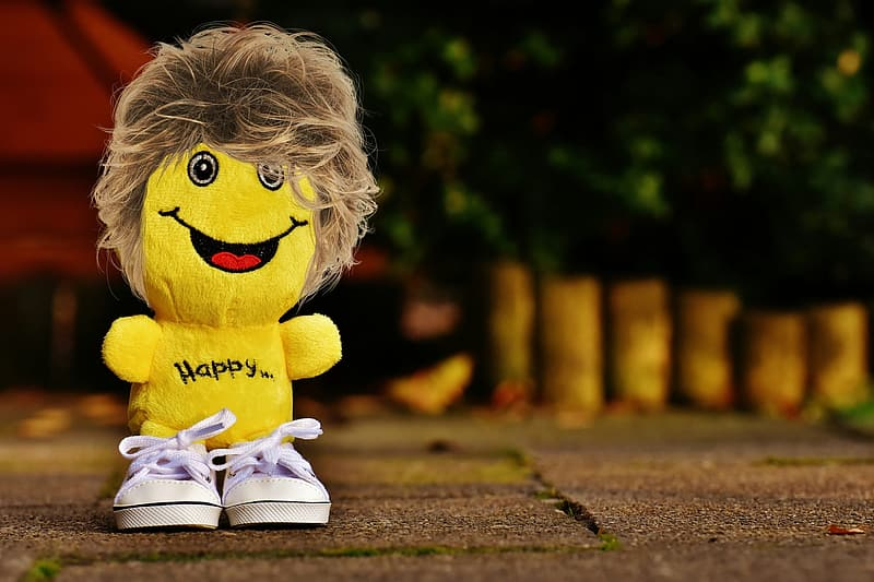 Selective focus photography of yellow plush toy on ground